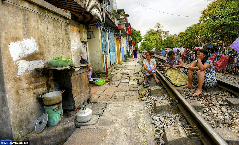 Unusual sight: The photographer said there are barbershops, people selling goods, chefs cooking food and kids running around - all within inches of the tracks