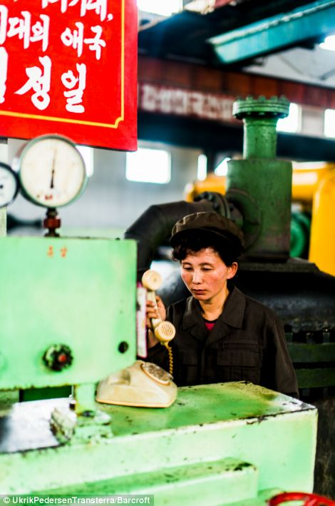 Hardly working? A woman in Hamhungs fertiliser factory answers a very old-fashioned telephone