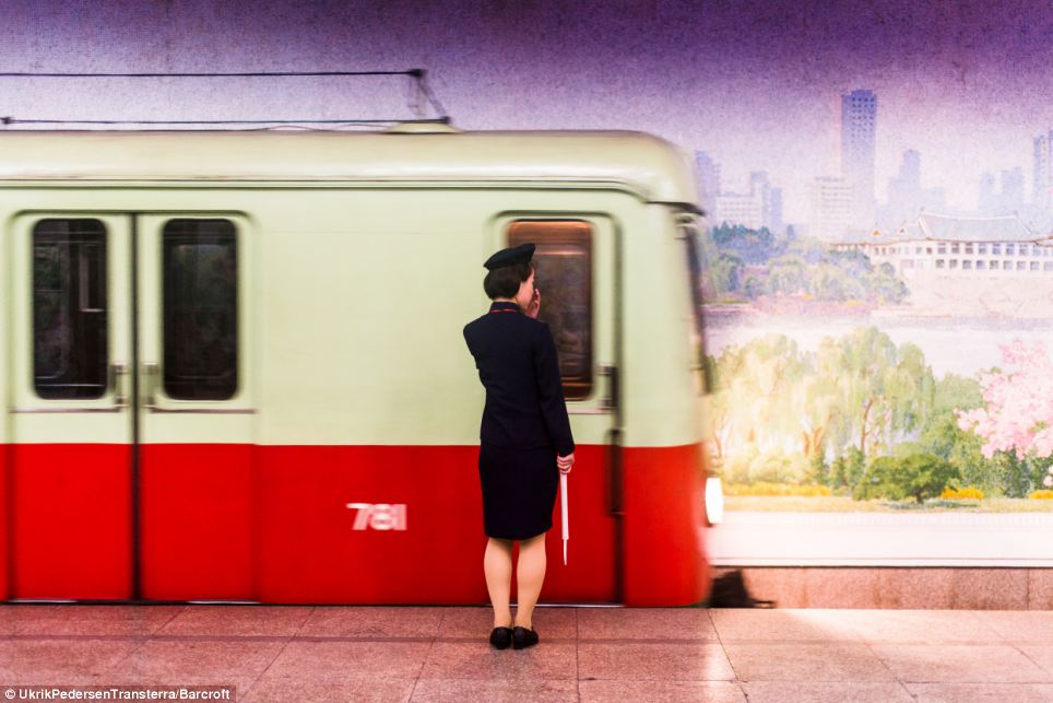 On the move: A female train guard waits for a train on North Koreas metro system in front of a mural painted on the far wall