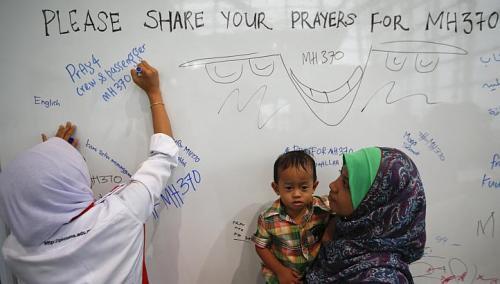 Một phụ nữ viết những lời cầu nguyện cho các nạn nhân bị mất tích. Ảnh: Reuters