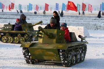Một người đàn ông cùng 1 đứa trẻ lái xe tăng đồ chơi trên sông băng Songhua  ở Cáp Nhĩ Tân, tỉnh Hắc Long Giang hôm 21-12-2013. Ảnh:EPA