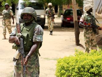 Binh lính Nigeria bảo vệ một ngôi trường tránh khỏi bị các phần tử cực đoan tấn công. Ảnh: AP