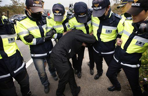 Cảnh sát Hàn Quốc chặn một thân nhân gia đình hành khách trong cuộc biểu tình kêu gọi một cuộc họp với Tổng thống Park Geun-hye. Ảnh: Reuters