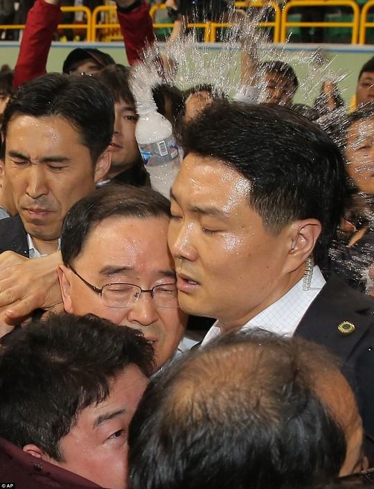 Thủ tướng Hàn Quốc bị thân nhân hành khách mất tích ném chai nước hôm 17-4 ở đảo Jindo. Ảnh: AP