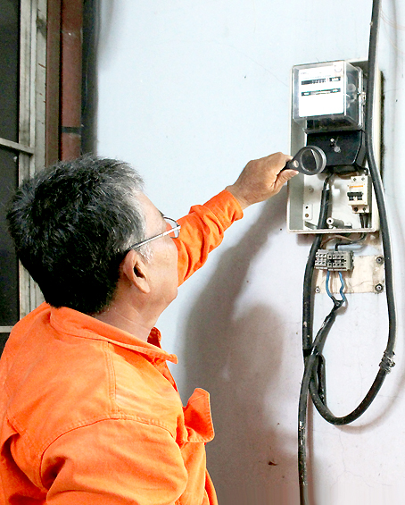 Nhân viên điện lực đang kiểm tra đồng hồ điện tại một nhà dân.