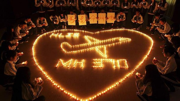 Heartbreak: International school students light candles  for passengers aboard Malaysia Airlines flight MH370, in Zhuji, Zhejiang province. The placards held by children read Pray for life.