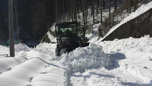 A grader of the Japan Ground Self-Defence Force removes snow covering a public road at Hinohara village, west of Tokyo, in this handout picture taken and released on Feb 17, 2014 by the Japan Ground Self-Defense Force. Snow-choked roads cut off thousands on Tuesday, Feb 18, 2014, as parts of Japan struggled to dig out from its second storm in a week, with the death toll rising to at least 23. -- PHOTO: REUTERS