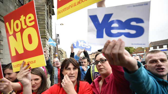 Pro and anti-independence supporters wave posters outside a campaign event in favour of the union in Clydebank, Scotland, September 16, 2014. (Reuters/Dylan Martinez)