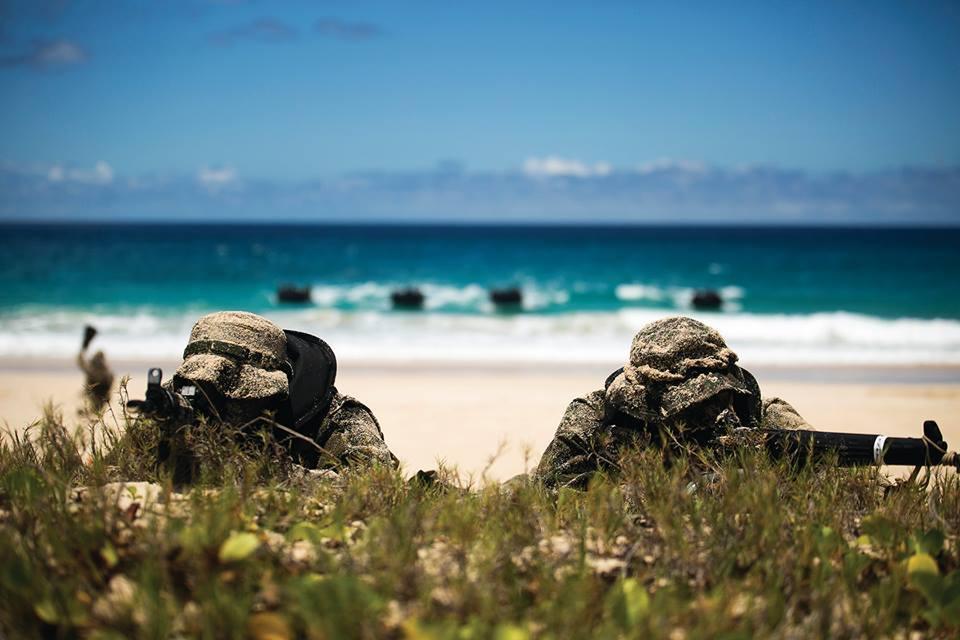 Hai lính phòng vệ Nhật Bản yểm trợ đồng đội di chuyển trên bờ trong một cuộc tấn công trên bộ.