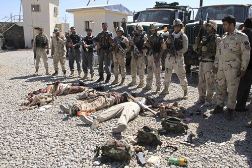 Afghan security forces gather around the bodies of dead Taliban insurgents at the site of a suicide attack in Ghazni Province September 4, 2014
