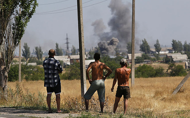 Cư dân chứng kiến cảnh những cột khói bốc lên trong vụ nã đạn pháo tại thị trấn Novoazovsk, đồng Ukraine hôm 27-8. Ảnh: AP