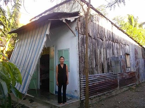 Bà Nguyễn Thị Bảy bên căn nhà rách nát ở cùng bà Nguyễn Thị Đèo vừa bị rút sổ hộ nghèo và sổ trợ cấp khuyết tật