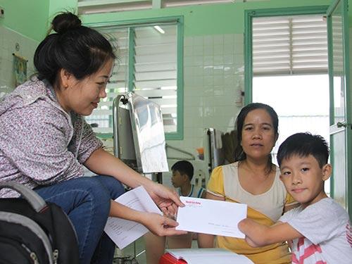 Đại diện Báo Người Lao Động trao tiền cho bé Nguyễn Gia Lâm