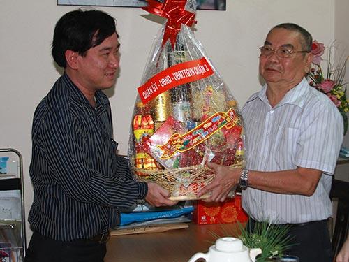 Ông Huỳnh Gia Giang (trái) - Chủ tịch UBND phường 6, quận 3,  TP HCM - trao quà cho ông Nguyễn Văn Muộn là thanh niên xung phong bị ảnh hưởng chất độc hóa học