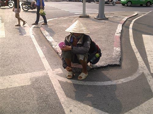 Một người đàn ông khỏe mạnh, lành lặn, đội nón lá lụp xụp cố tình che giấu khuôn mặt... còn trẻ ngồi chờ bố thí tại ngã tư Bảy Hiền (quận Tân Bình)
