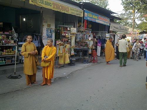 Một nhóm sư giả đứng trước con đường dẫn vào chùa Hoằng Pháp (huyện Hóc Môn) để khất thực
