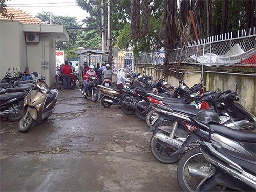 Mặc dù treo bảng giữ xe miễn phí nhưng nhân viên bãi giữ xe ở UBND quận Bình Thạnh, TP HCM vẫn thu 3.000 đồng/xe máy
