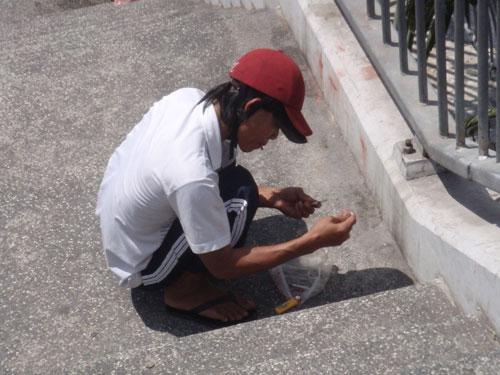 Một người nghiện đang chích ma túy ngay cầu thang bộ hành trên cầu Chà Và Ảnh: TÂN TIẾN