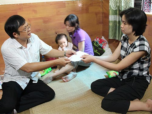 Ông Phạm Hồng Kỳ, Trưởng Văn phòng Đại diện Báo Người Lao Động tại Hà Nội, trao quà cho vợ của đại úy Nguyễn Đào Hồng Tâm Ảnh: NGỌC DUNG
