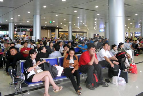Hành khách ngồi chờ lên máy bay (nhà ga quốc nội Tân Sơn Nhất) Ảnh: TẤN THẠNH
