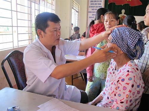 Bác sĩ đang khám bệnh cho một phụ nữ dân tộc S'tiêng
