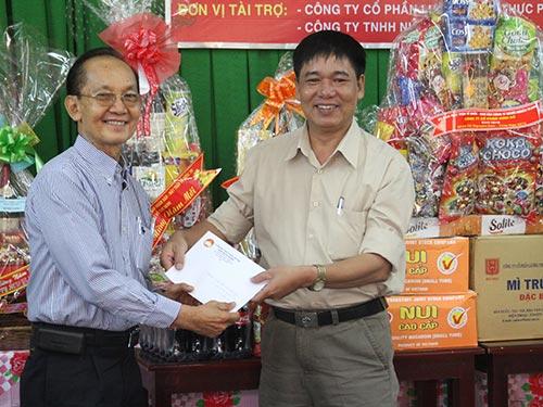 Bác sĩ Trần Đông A, Ủy viên MTTQ TP HCM (trái), trao quà cho đại diện Làng Thiếu niên Thủ Đức vào sáng 23-1