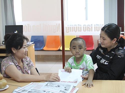 Cháu Hồ Thanh Hoàng và mẹ nhận tiền hỗ trợ của bạn đọc Báo Người Lao Động