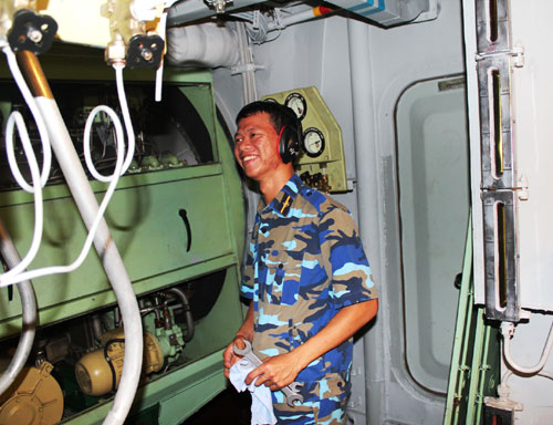 Một thủy thủ túc trực bên tiếng máy tàu ở hầm máy.