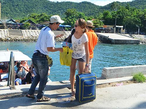 Hướng dẫn viên nhắc nhở một du khách nước ngoài khi người này mang túi ni-lông lên đảo và hướng dẫn thay túi tự hủy