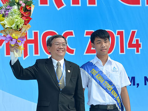 PGS-TS Vũ Đình Thành nhận hoa chúc mừng của thủ khoa trong kỳ tuyển sinh ĐH-CĐ vào trường năm 2014