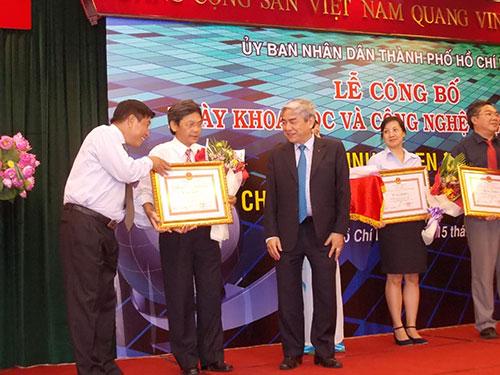 Bộ trưởng Bộ Khoa học và Công nghệ Nguyễn Quân và ông Phan Minh Tân, Giám đốc Sở Khoa học và Công nghệ TP HCM (áo trắng, trái), trao bằng khen cho các cá nhân, tập thể được vinh danh
