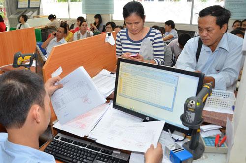Doanh nghiệp làm thủ tục kê khai thuế tại Cục Thuế TP HCM Ảnh: TẤN THẠNH