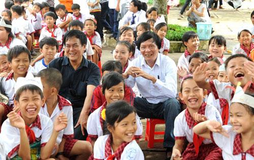 Nhà văn Nguyễn Đông Thức và nhà văn Đoàn Thạch Biền (áo trắng) giữa các học trò nhỏ ở Trường Tiểu học Tân Hạnh, huyện Long Hồ, tỉnh Vĩnh Long
