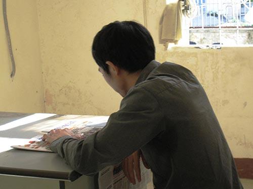 Bị cáo Nguyễn Thân Thảo Thành thản nhiên ngồi đọc báo