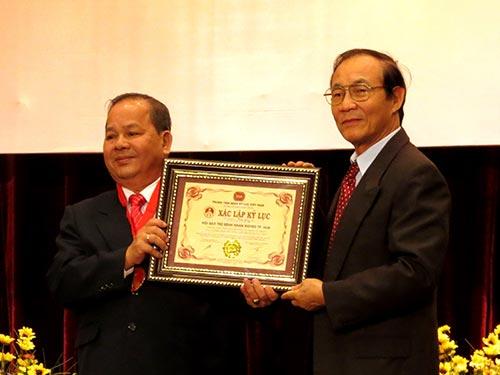 Ông Trần Hữu Tâm, Phó Chủ tịch Hội Bảo trợ bệnh nhân nghèo TP HCM (trái), thay mặt hội đón nhậnKỷ lục Guinness Việt Nam về số ca phẫu thuật mắt miễn phí