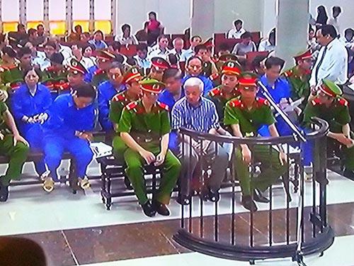 Bị cáo Nguyễn Đức Kiên và đồng phạm tại phiên tòa ngày 23-5. (Ảnh chụp qua màn hình)