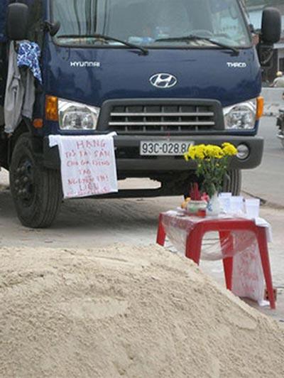 Viết yêu cầu đòi nợ treo trước xe tải (ảnh lớn) và trên áo (ảnh nhỏ) Ảnh: Như Phú