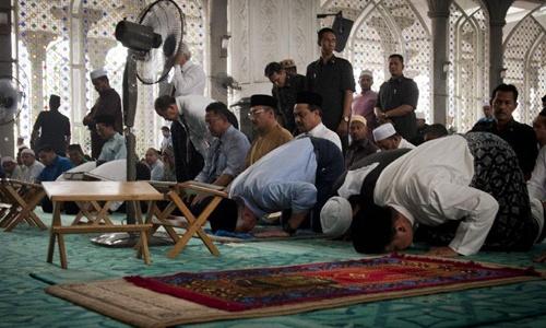 Thủ tướng Malaysia Najib Razak (thứ ba từ phải sang) dập đầu cầu nguyện cho những người trên chuyến MH370 tại một ngôi đền gần sân bay quốc tế Kuala Lumpur hôm 14-3. Ảnh: Tân Hoa Xã