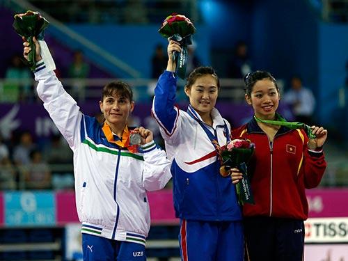 Hà Thanh (phải) trên bục nhận HCĐ nội dung nhảy chống môn thể dục dụng cụ  Ảnh: REUTERS