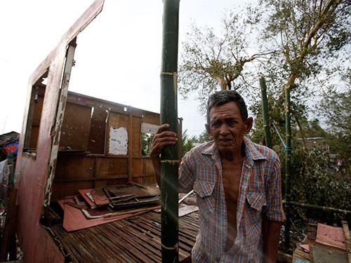 Một người dân đứng trước ngôi nhà bị bão Rammasun tàn phá ở thành phố Batangas - Philippines hôm 17-7 Ảnh: REUTERS