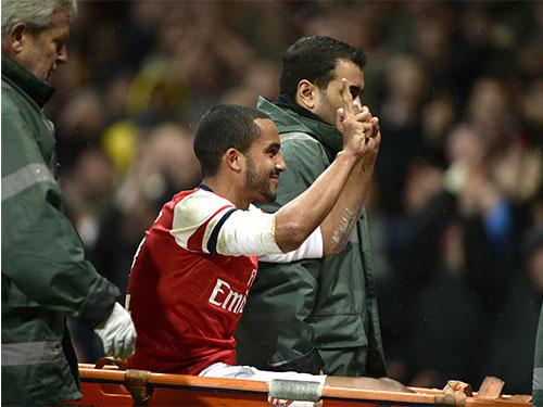 Walcott mỉm cười chọc tức CĐV Tottenham sau khi bị ném đồng xu Ảnh: REUTERS