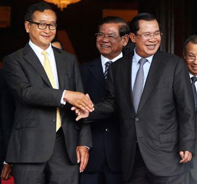 Thủ tướng Campuchia Hun Sen (phải) bắt tay ông Sam Rainsy sau cuộc gặp hôm 22-7 Ảnh: REUTERS
