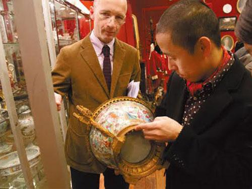 Một khách hàng Trung Quốc xem xét đồ cổ tại nhà đấu giá Drouot ở Pháp Ảnh: CHINA DAILY