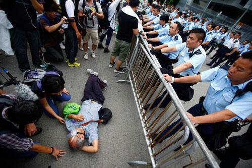 Một người biểu tình nằm trước lối vào trụ sở chính quyền Hồng Kông hôm 2-10 Ảnh: REUTERS