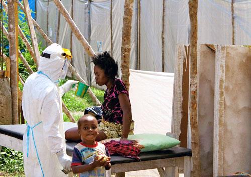 Một nhân viên y tế cung cấp nước cho một phụ nữ nhiễm virus Ebola tại một trung tâm điều trị ở TP Kenema - Sierra Leone Ảnh: REUTERS