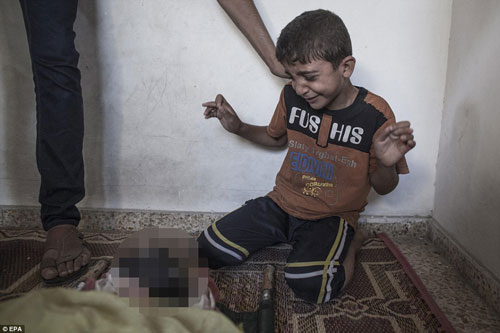 Cậu bé người Palestine trào nước mắt khi nhìn thấy thi thể người thân thiệt mạng trong vụ tấn công của Israel vào trường học của Liên Hiệp Quốc Ảnh: EPA