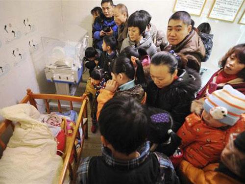 Người dân đến thăm một đứa bé bị bỏ rơi ở nhà trẻ tình thương thuộc TP Quý Dương, tỉnh Quý Châu Ảnh: REUTERS