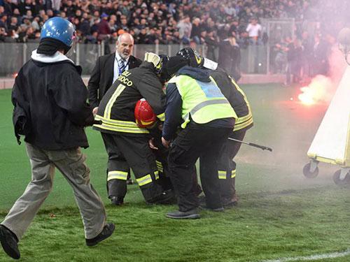 Cảnh sát Ý dìu một đồng nghiệp bị thương vì bom khói  Ảnh: GAZZETTA DELLO SPORT
