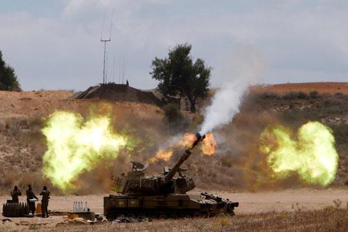 Quân đội Israel bắn đạn pháo về phía Dải Gaza hôm 18-7 Ảnh: REUTERS