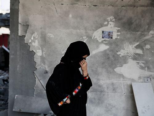 Một phụ nữ Palestine nghẹn ngào trước đống đổ nát của nhà mình tại Gaza. Ảnh: Reuters